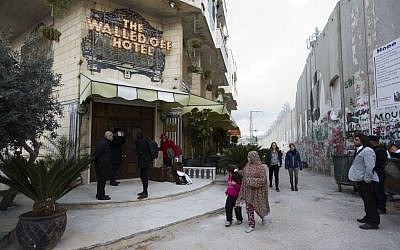 People pass by 'The Walled Off Hotel' and the Israeli security barrier in the West Bank city of Bethlehem, Friday, March 3, 2017.  (AP Photo/Dusan Vranic)