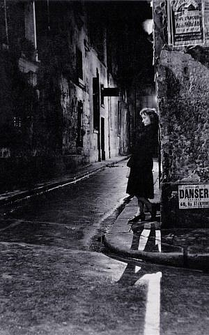 A woman in Paris at night, a photo by Adolfo Kaminsky. (Courtesy)