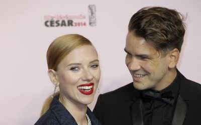 In this February 28, 2014, photo, US actress Scarlett Johansson, left, and her partner Romain Dauriac arrive at the 39th French Cesar Awards Ceremony, in Paris. (AP Photo/Lionel Cironneau, File)