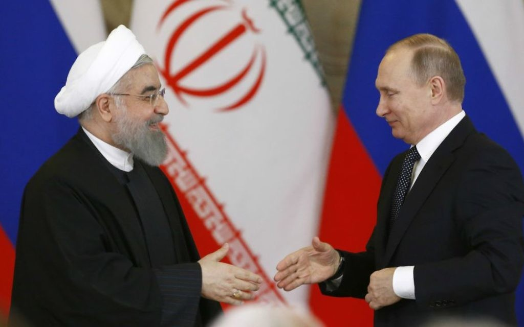 Russian President Vladimir Putin, right, shakes hands with Iranian President Hassan Rouhani during a joint news conference at the Kremlin in Moscow, Russia, March 28, 2017. (Sergei Karpukhin/Pool photo via AP)