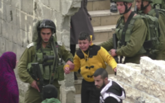 A Palestinian boy being led through the streets of Hebron, whom the army says is suspected of throwing a firebomb at a Jewish settlement, on March 21, 2017. (Screen capture: B'Tselem)