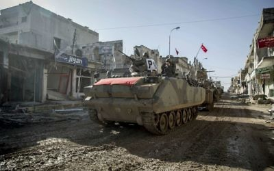 In this February 22, 2015, file photo, Turkish military vehicles and tanks drive in the Syrian town of Ayn al-Arab, also known as Kobani, Syria. (AP Photo/Mursel Coban, Depo Photos, File)