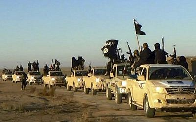 In this undated file photo released by a militant website, which has been verified and is consistent with other AP reporting, militants of the Islamic State group hold up their weapons and wave flags on their vehicles, in a convoy on a road leading to Iraq, from Raqqa, Syria. (Militant website via AP)