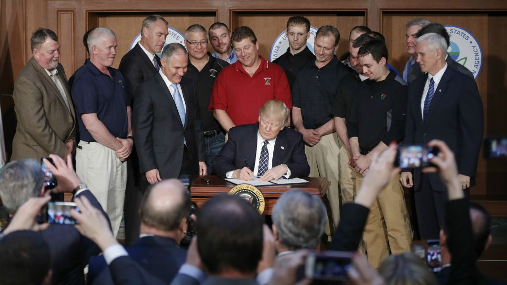 President Donald Trump, accompanied by Environmental Protection Agency (EPA) Administrator Scott Pruitt, third from left, and Vice President Mike Pence, right, signs an Energy Independence Executive Order, March 28, 2017, at EPA headquarters in Washington. (AP Photo/Pablo Martinez Monsivais)