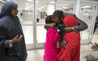 Ismail Issack, father of Miski Shalle, 11, and Muzamil Shalle, 14, embraces his children as their mother Halima Mohamed, far left, looks on as they reunite for the first time in seven years at John F. Kennedy International Airport in New York Wednesday, March 8, 2017. (AP Photo/Craig Ruttle)