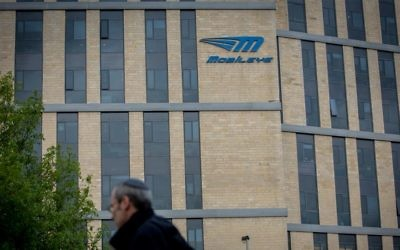 A man walks under the Mobileye logo in Jerusalem, March 13, 2017. (Yonatan Sindel/Flash90)