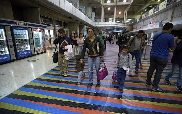 In this March 17, 2017 photo, Jewish converts Sahir Quitero, center, her husband Franklin Perez, son Ezra, left, and daughter Hannah, walk to departures lounge of the Simon Bolivar International Airport in Maiquetia, Venezuela, on their way to Israel. (AP Photo/Fernando Llano)