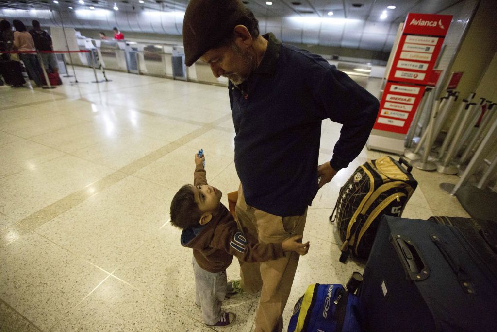In this March 17, 2017 photo, Franklin Perez speaks with his son Ezra as they wait for a flight to Bogota on their way to Israel, at the Simon Bolivar International Airport in Maiquetia, Venezuela. (AP Photo/Fernando Llano)
