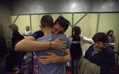 In this March 17, 2017 photo, Jose Luis Garcia embraces and cries as he says goodbye to his little brother that departs to Bogota on his way to Israel, at the Simon Bolivar International Airport in Maiquetia, Venezuela. (AP Photo/Fernando Llano)
