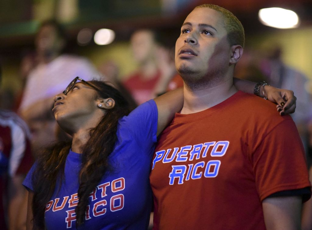 People gather to watch television coverage of the World Baseball Classic final between Puerto Rico and the United States, in San Juan, Puerto Rico, Wednesday, March 22, 2017. The United States won 8-0. (AP Photo/Carlos Giusti)