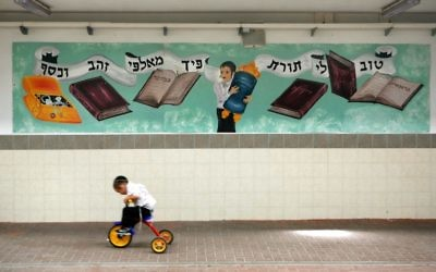 An illustrative photo of a boy riding his bike past a mural about the importance of Torah in Beitar Ilit. (Nati Shohat /Flash90)