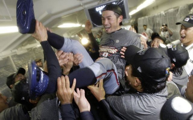 FILE - In this March 23, 2009, file photo, Japan's Ichiro Suzuki gets tossed around by teammates during a clubhouse celebration after their 5-3 victory over South Korea in the championship game of the World Baseball Classic, in Los Angeles. (Ted S. Warren/AP/Pool)