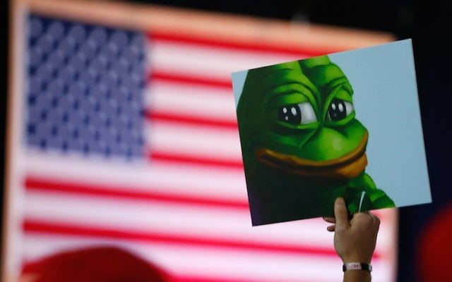 A Donald Trump supporter holds a cartoon designated a hate symbol by the anti-defamation league before the start of a campaign event in Bedford, NH, on Sept. 29, 2016.  (Jessica Rinaldi/The Boston Globe via Getty Images)