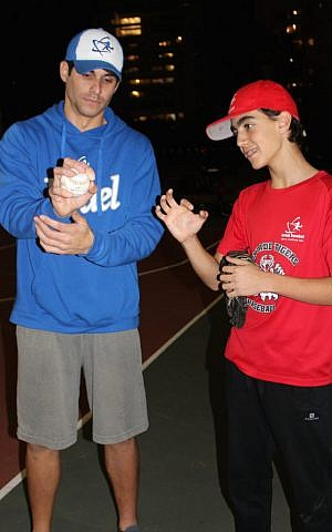 Alejandro Eskenazi demonstrates to an Israeli youngster the proper grip to throw a change-up. (Hillel Kuttler/via JTA)