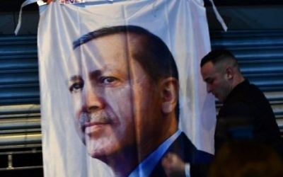 A man gestures in front of a flag bearing a portrait of Turkish President Recep Tayyip Erdogan as Turkish residents of the Netherlands protested outside Turkey's consulate in Rotterdam on March 11, 2017. / AFP PHOTO / Emmanuel DUNAND