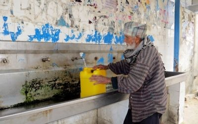 An elderly Palestinian man fills a water container at a public tap at the Khan Yunis Water Authority's wastewater treatment plant. (CC-BY-4.0 Muhammad Sabah B'Tselem/Wikipedia)