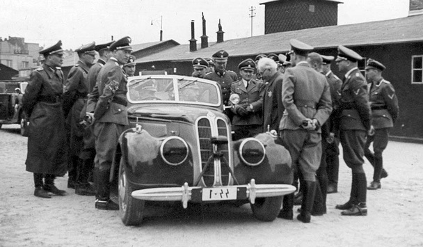 As chairman of the Lodz ghetto's Nazi-appointed Jewish Council, Chaim Rumkowski (standing, center) greeted SS chief Heinrich Himmler (seated in automobile) during the latter's visit to Rumkowski's 'industrialized' ghetto (Public domain)