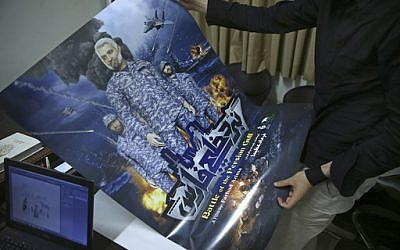 """In this Sunday, Feb. 26, 2017 photo, a production assistant for the animated film, """"Battle of the Persian Gulf II,"""" holds a poster for the movie, at the office of Farhad Azima, the Iranian director and screenwriter, in Tehran, Iran. (AP Photo/Vahid Salemi)"""