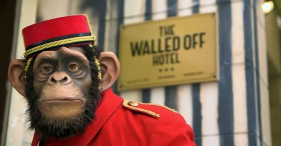 The monkey sculpture wearing a bell-hop uniform that stands outside the artist Banksy's new Bethlehem hotel in the West Bank. (Screen capture/YouTube)