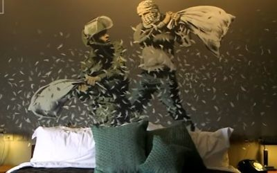 Banksy's depiction of a pillow-fight between an Israeli soldier and a Palestinian that is painted on the wall of one of the room's in the artist Banksy's new Bethlehem hotel in the West Bank (Screen capture/YouTube)