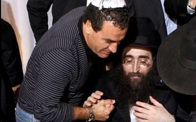 Head of the police's 433 Lahav anti-corruption unit Menashe Arviv (L) pictured embracing Rabbi Yoshiyahu Pinto (Screen capture/YouTube)