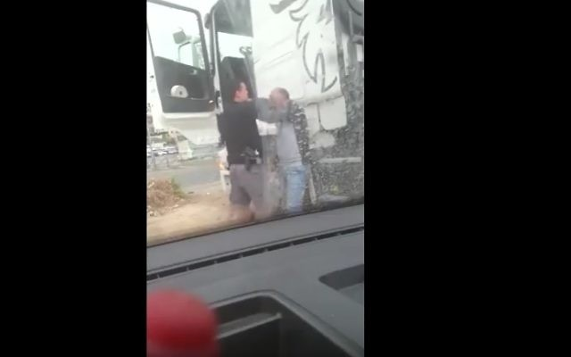 A still from a video showing a police officer assaulting an East Jerusalem truck driver (YouTube screenshot)