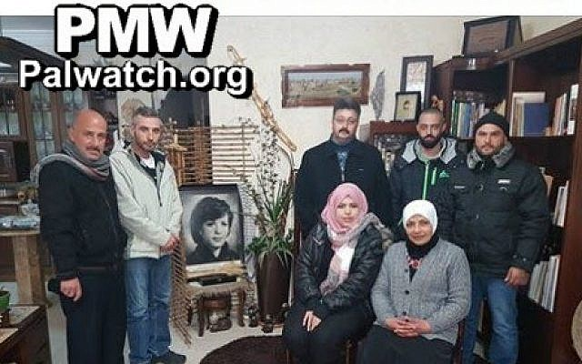 Organizers of the 'Brothers of Dalal' youth camp pose beside photo of terrorist Dalal Mughrabi (PMW)