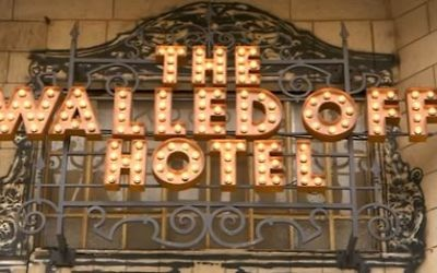 The lit-up sign at the front of Banksy's Walled Off Hotel in Bethlehem. (Screen capture/YouTube)