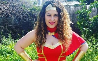 Illustrative: A woman showing off her Wonder Woman costume outside a friend's house in Tel Aviv before the city's big Purim party, March 10, 2017. (Courtesy of Eilit Rozin via JTA)