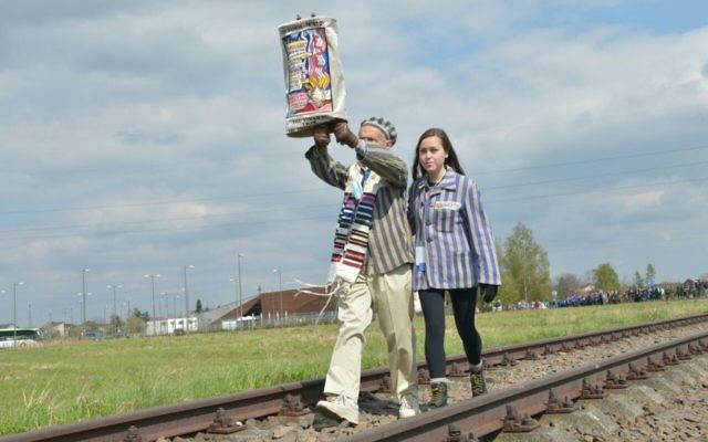 A survivor and his granddaughter walk with a Torah in the March of the Living near Auschwitz-Birkenau on April 24, 2017. (Yossi Zeliger/ Flash90)
