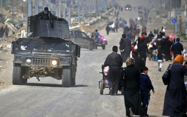 Iraqi security forces drive past civilians fleeing their homes in Mosul's old city on March 30, 2017, due to the ongoing battles between government forces and Islamic State (IS) group fighters. (AFP/Ahmad Gharabli)