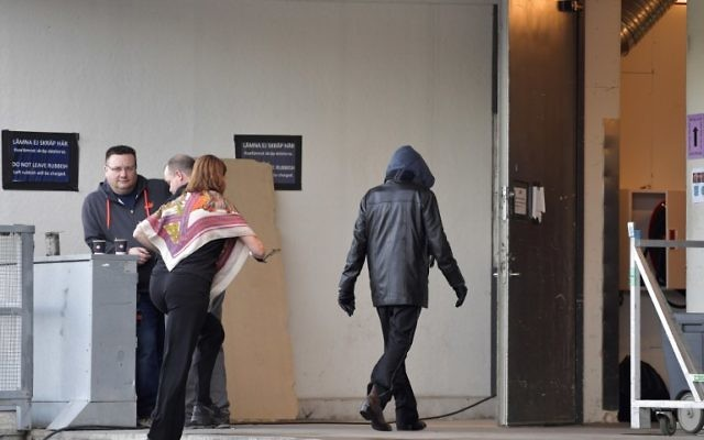 A person assumed to be Bob Dylan, wearing a black jacket and a hoodie, enters the backstage door at Stockholm Waterfront April 1, 2017 (AFP PHOTO / TT News Agency / Jessica GOW)