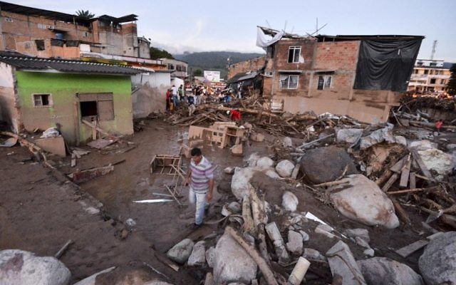 People walk through the rubble left by mudslides following heavy rains in Mocoa, Putumayo department, southern Colombia on April 1, 2017 (AFP PHOTO / LUIS ROBAYO)