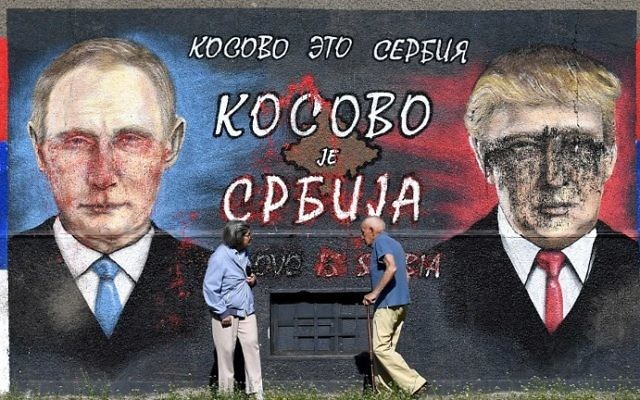"People walk past a wall depicting Russian President Vladimir Putin (L) and US President Donald Trump with a message in cyrillic letters reading ""Kosovo is Serbia"" in Belgrade on April 2, 2017. (AFP Photo/Andrej Isakovic)"