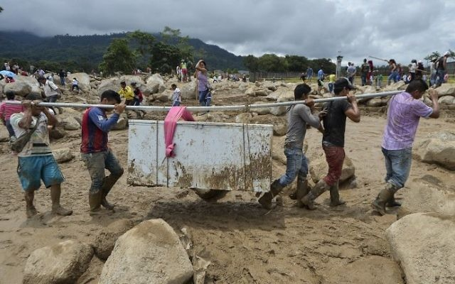 People carry their belongings amidst the rubble left by mudslides following heavy rains in Mocoa, Putumayo department, southern Colombia on April 2, 2017. (AFP PHOTO / LUIS ROBAYO)