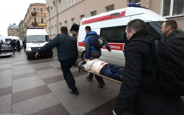Men carry an injured person on a stretcher outside the Technological Institute metro station in Saint Petersburg on April 3, 2017. (AFP Photo/Inter Press/Alexander Tarasenkov)