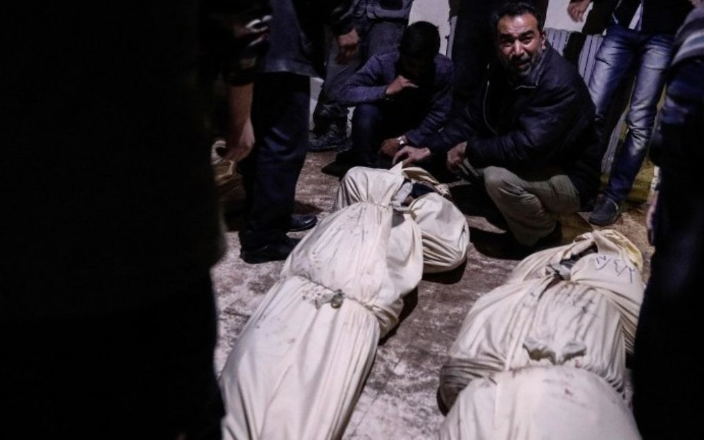 Relatives react as they identify bodies of victims following reported air strikes by government forces in the rebel-held town of Douma, on the eastern outskirts of Damascus, on April 3, 2017. (AFP PHOTO / Sameer Al-Doumy)