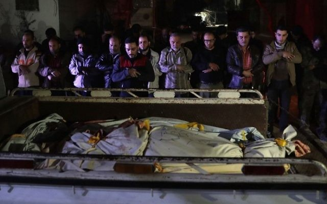 Syrian mourners pray next to bodies lying in the back of a pick up truck outside a makeshift morgue following reported air strikes by government forces in the rebel-held town of Douma, on the eastern outskirts of Damascus, on April 3, 2017. (AFP PHOTO / Abd Doumany)