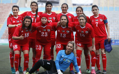 Palestinian female soccer players (in red) are seen during a qualifying match against Thailand for the Asian Women football Cup in the West Bank town of al-Ram on April 3, 2017.  (AFP PHOTO / ABBAS MOMANI)