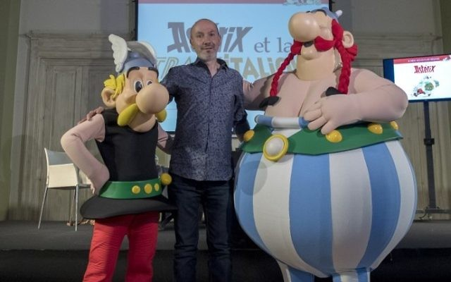 French comics writer, designer and colourist Jean-Yves Ferri poses with comic book characters Asterix, left, and Obelix, right, after a press conference 37th album of the Asterix series in Bologne, April 5, 2017. (AFP/MIGUEL MEDINA)