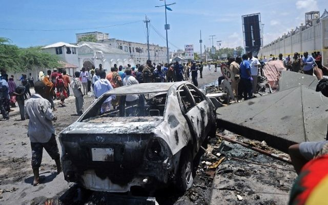 Illustrative: People stand at the site of a car bomb near a restaurant near the Somali ministry of internal security in Mogadishu on April 5, 2017. (AFP Photo/Mohamed Abdiwahab)