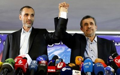 Former Iranian president Mahmoud Ahmadinejad (R) and his former vice president, Hamid Baghaie, lock hands during a press conference in the capital Tehran on April 5, 2017. (AFP Photo/Atta Kenare)
