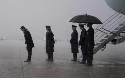 A secret service officer (L) and Air Force personnel wait outside Air Force One in the rain for the arrival of US President Donald Trump at Andrews Air Force Base, Maryland, April 6, 2017. (AFP/Jim Watson)