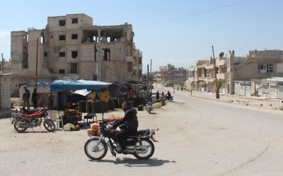 A Syrian man rides his motorcycle in Khan Sheikhun on April 7, 2017 near the area of a suspected chemical weapons attack earlier this week on the northwestern Syrian town that killed at least 86 people. (AFP/Omar Haj Kadour)