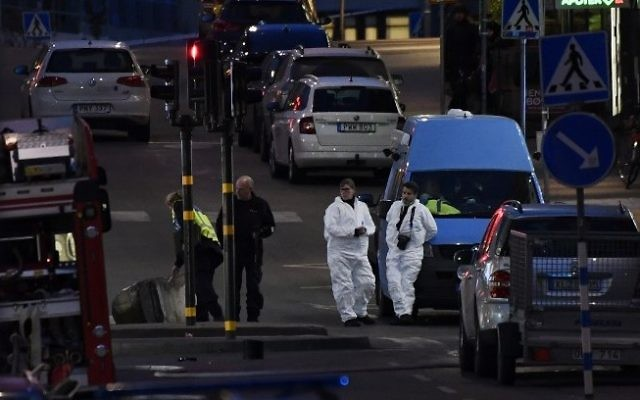 """Forensics Police officers work at the scene where a truck slammed into a crowd of people outside a busy department store in central Stockholm, causing """"deaths"""" in what the prime minister described as a 'terror attack' on April 7, 2017.  (AFP/ Jonathan NACKSTRAND)"""