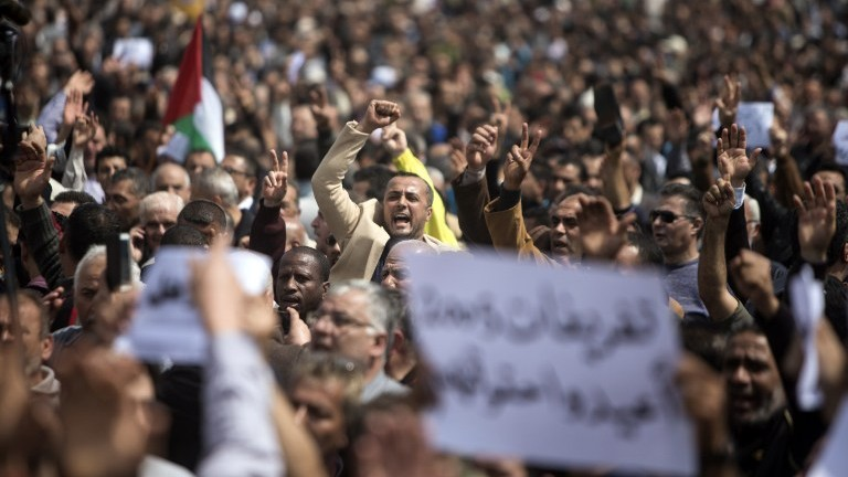 Palestinian Authority employees chant slogans and wave placards during a demonstration against the decision by the PA to reduce their salaries in Gaza City on April 8, 2017. (AFP Photo/Mahmud Hams)