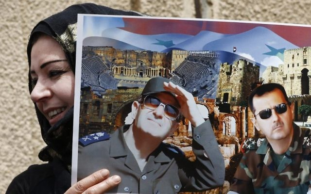 A Syrian protester holds a poster bearing images of the Syrian President (R) and his late father and former president of Syria during a demonstration in support of the governing family outside the United Nation's (UN) office in the capital Damascus on April 8, 2017. (AFP PHOTO / Louai Beshara)