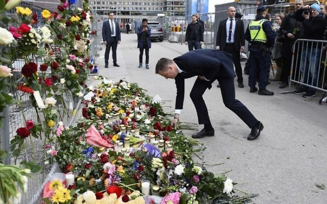 Swedish Social democrat politician Anders Ygeman lays flowers at a makeshift memorial near the site where a truck slammed into a crowd yesterday outside a busy department store, in central Stockholm, on April 8, 2017.  (AFP PHOTO / Jonathan NACKSTRAND)