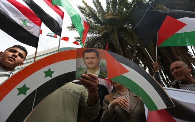 Palestinian supporters of the Palestine Liberation Organization wave Palestinian and Syrian flags alongside a portrait of Syrian President Bashar Assad as they demonstrate on April 9, 2017 in the center of the West Bank city of Nablus against US air strikes on Syria. (AFP/JAAFAR ASHTIYEH)