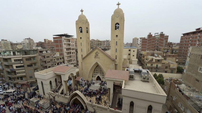 A general view shows people gathering outside the Mar Girgis Coptic Church in the Nile Delta City of Tanta, north of Cairo, after a bomb blast struck worshippers gathering to celebrate Palm Sunday on April 9, 2017. (AFP Photo/Khaled Desouki)